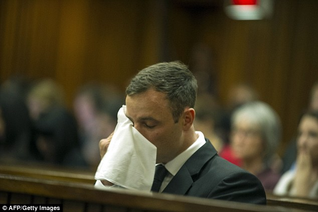 Emotional day in court: Pistorius wipes away tears as defence lawyer Barry Roux tells the court of the runner's dramatic fall from 'a sporting icon' to appearing in the media as 'a cold-blooded killer'