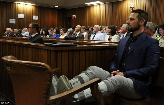 By his brother's side: Carl Pistorius (pictured earlier this week) sits next to the dock with his legs propped up in splints after he was involved in a car crash that left him in a coma earlier this year