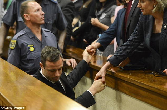 Taken down: Oscar Pistorius says his final goodbyes to his family as he is escorted to the holding cells at the high court in Pretoria after being sentenced to five years in prison for killing his girlfriend Reeva Steenkamp