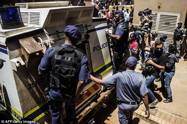 Heavy security: Pistorius was driven to jail in an armoured police van, with tactical response guards hanging on