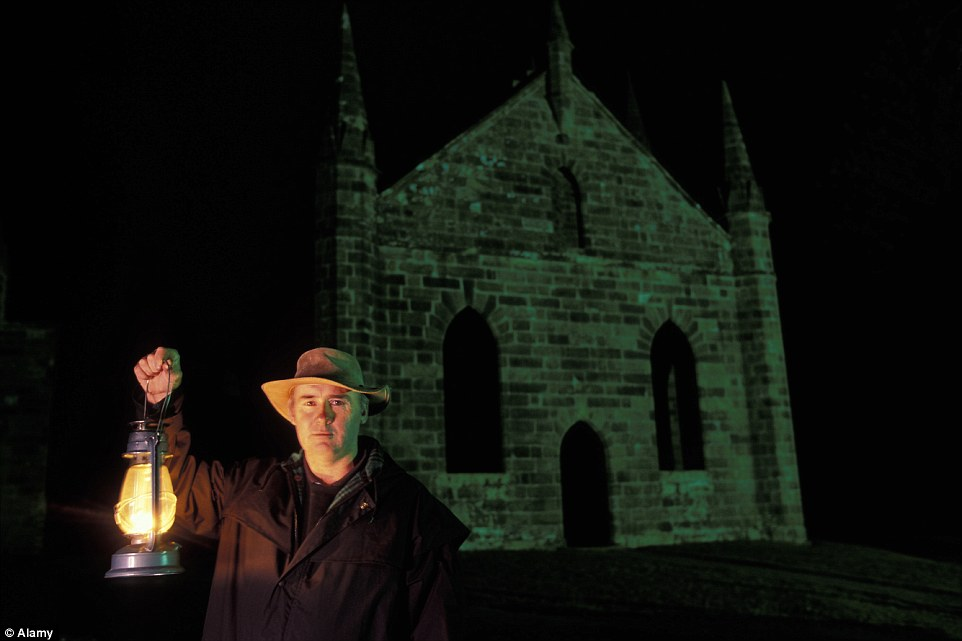 Paul Cooper holds a lantern during a spooky Ghost Walk in front of old church at Port Arthur Prison