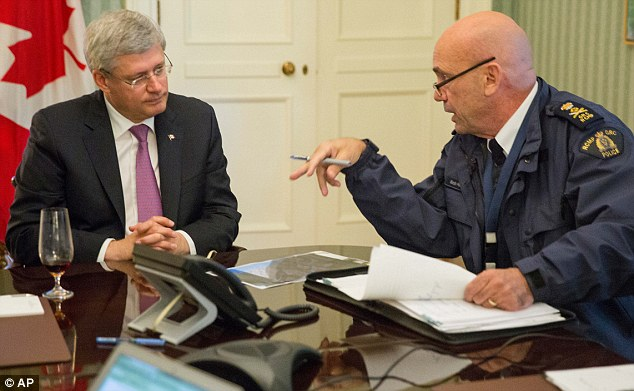 Briefed: The head of RCMP Bob Paulson briefs Canadian Prime Minister Stephen Harper on the shootings