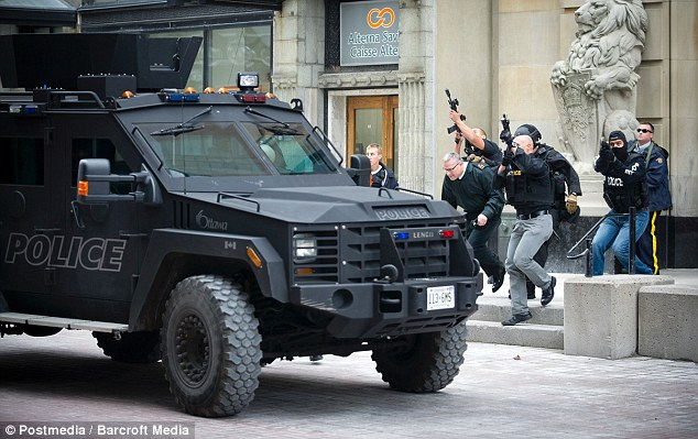 Guns raised: Emergency responders escort VIPs out of building on Sparks Street near the Post Office