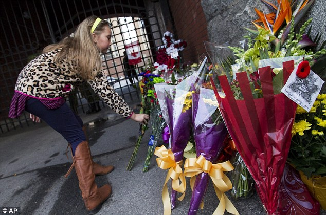In memory: A young girl places a flower outside the gates of John Weir Foote Armory in honor of Corporal Cirillo