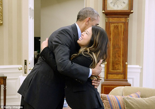 President Barack Obama gives a hug to Dallas nurse Nina Pham in the Oval Office of the White House on Friday, the day she was declared free of the virus
