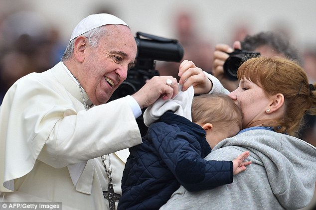 Spooked: Pope Francis scares a child as he tries to greet him during his general audience at St Peter's square. The Vatican has called for Halloween to be called 'Holyween' to cut the amount of occult acitivity