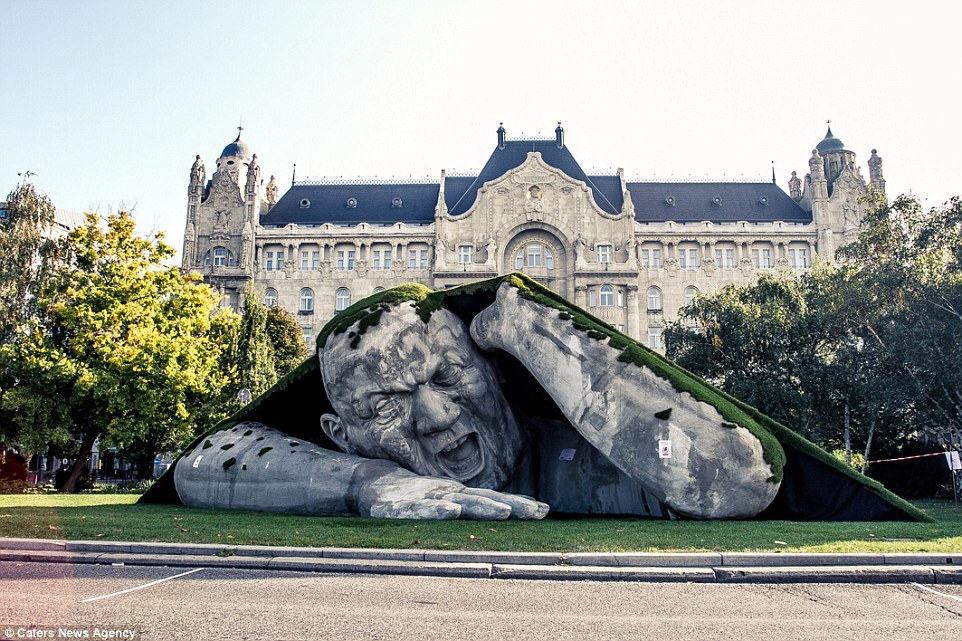From deep below: A giant man emerges from beneath a square in Budapest