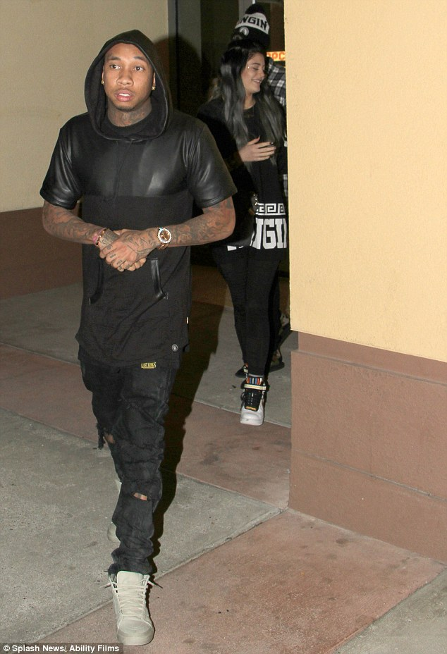 We can see you! Rapper Tyga emerges from a cinema in Los Angeles, with Kylie Jenner walking just a few steps behind