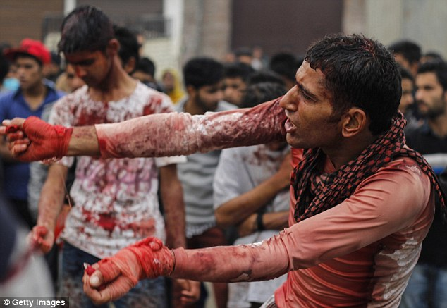 Men were seen drenched in blood as they observed the tradition, as hundreds of onlookers watched
