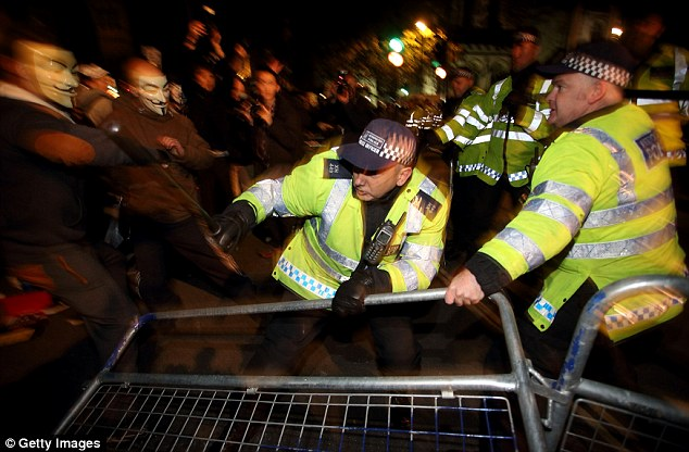 A police officer ducks to avoid the pushing and shoving which surged through the crowd during the protest
