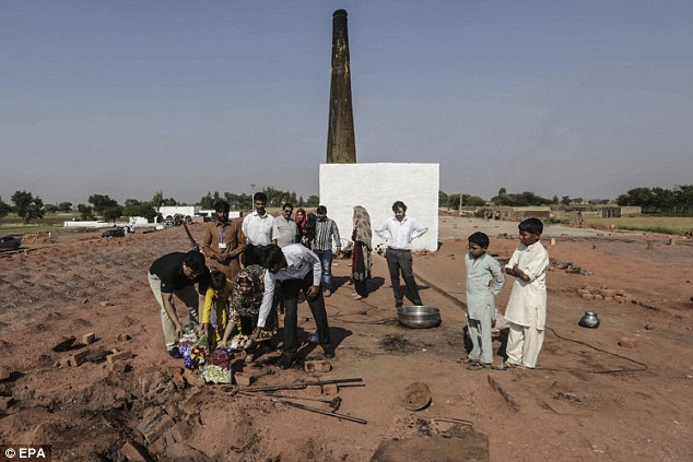 Pakistani Christians lay floral wreaths at the brick kiln where a Christian couple was burnt alive