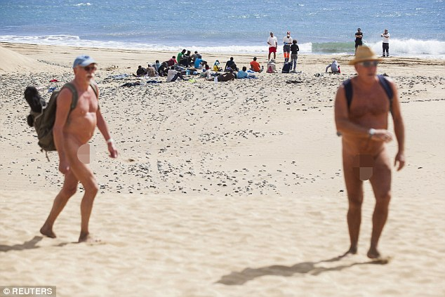 Nudists look on in shock as the group of migrants are kept isolated by the water's edge