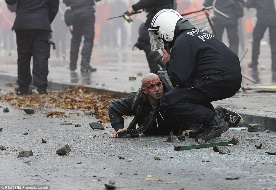 Violent: A policeman crouches over an injured demonstrator as lines of police push back protesters