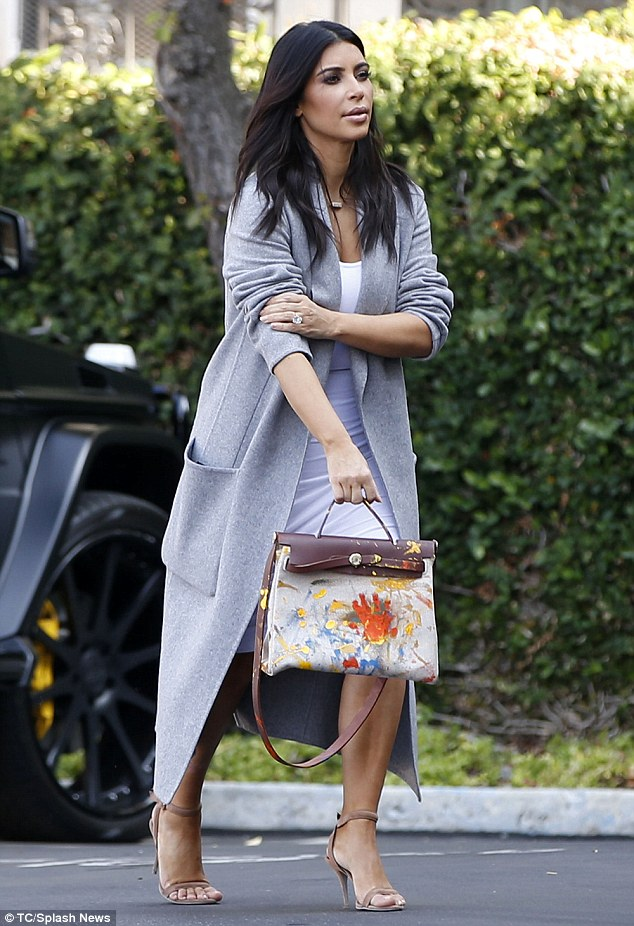 Keeping her close: Kim Kardashian carried a handbag that appeared to have been painted by her daughter North on Monday in LA