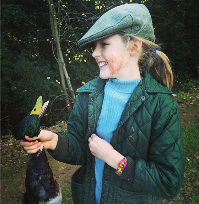 Her first kill: With blood smeared across her face, a smiling Cece, 10, poses with the dead duck