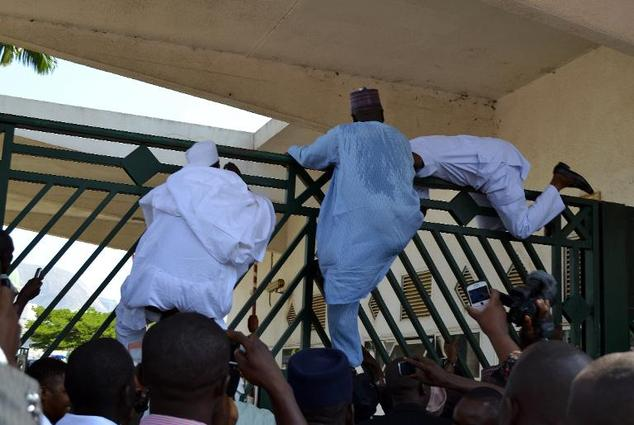 Nigerian parliament members climb the assembly gate, which was closed by security forces, in Abuja on November 20, 2014
