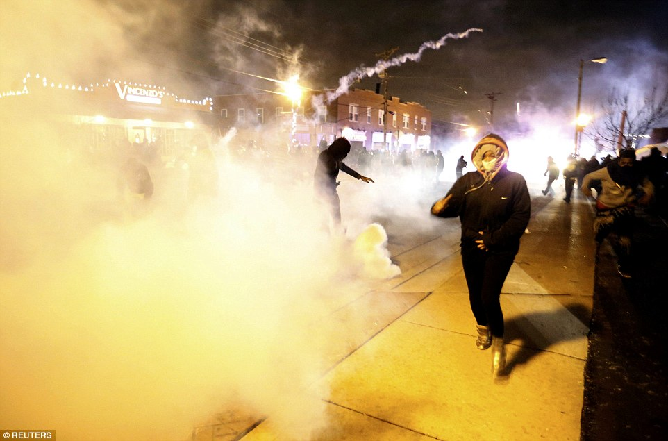 Harder to breathe: Protesters run from a cloud of tear gas Monday night in Ferguson, Missouri, where local police are trying to control violent crowds