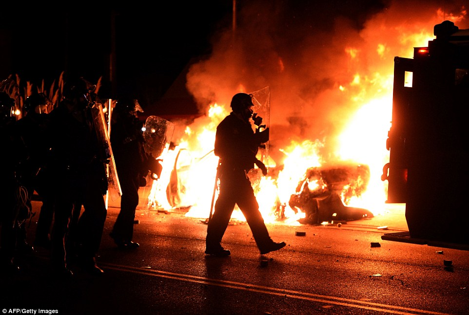 Up in flames: Police in riot gear stand near a burning car on a street in Ferguson on Monday. Moments after the announcement by St. Louis County's top prosecutor, crowds began pouring into Ferguson streets to protest the decision