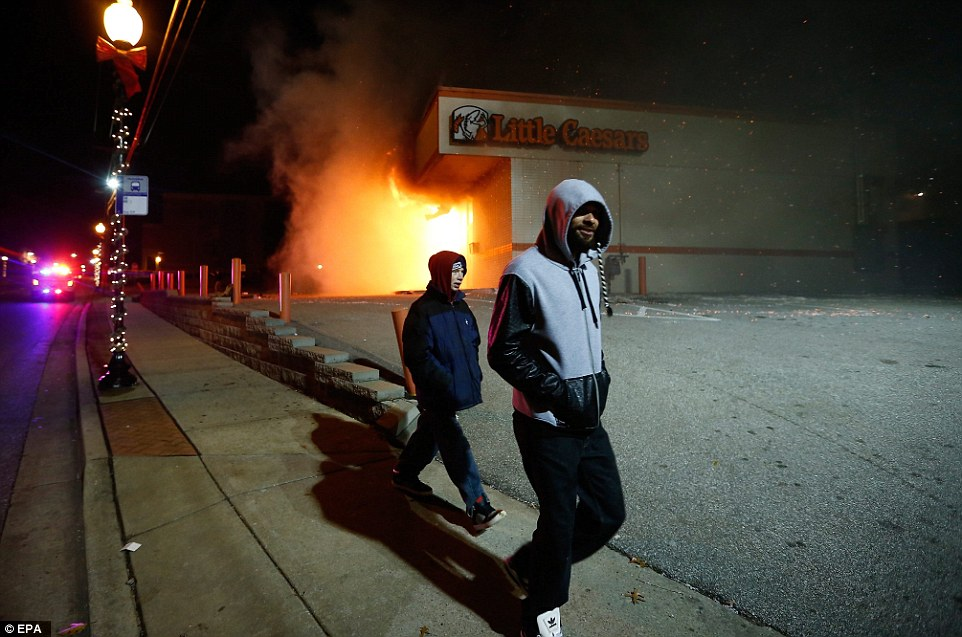 Arson: Two men walk by the burning Little Caesars restaurant in Ferguson Missouri, USA, on 24 November after violence flared again in the St. Louis suburb of Ferguson on Monday, with gunshots heard and tear gas fired, after a Missouri grand jury decided not to indict a white police officer over the fatal shooting of an unarmed black teenager in August