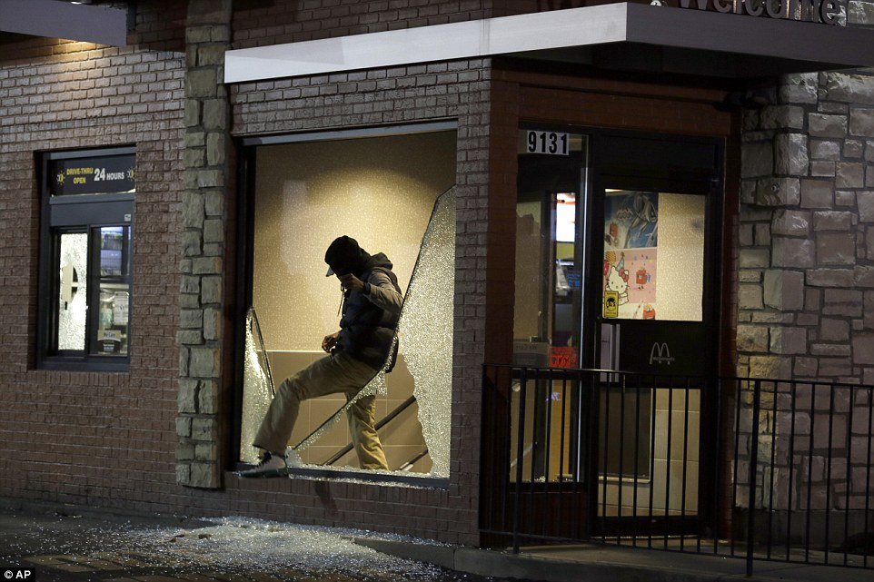 Helping himself: A man steps out of a vandalized store after the announcement of the grand jury decision Monday, Nov. 24, 2014, in Ferguson, Missouri