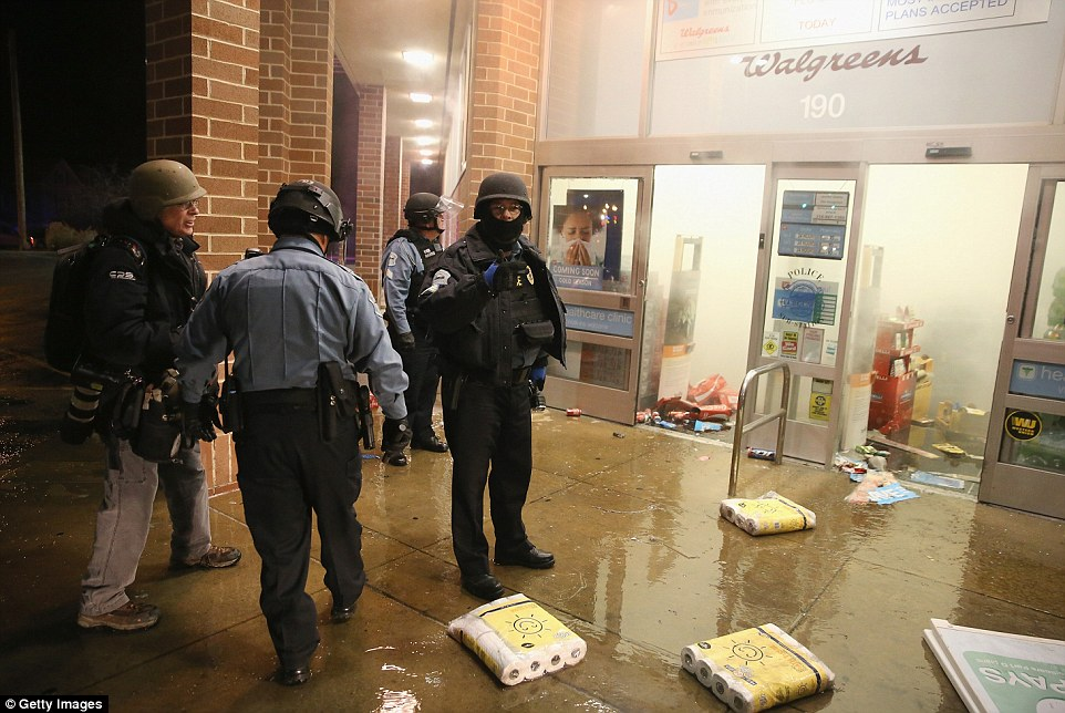 Police search for looters at a burning Walgreens store which was set on fire by protestors