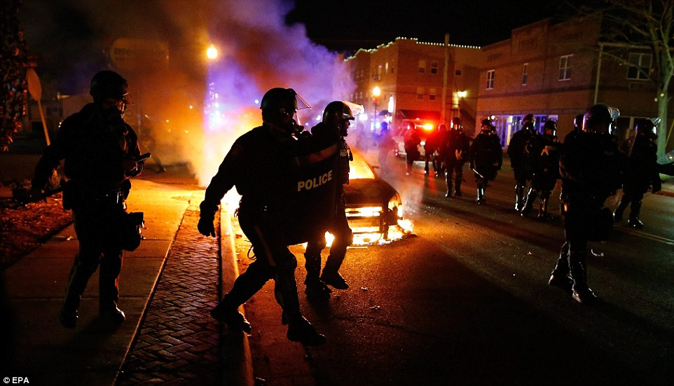 Out of control: Police in riot gear move past a vehicle that continues to burn on the street in Ferguson