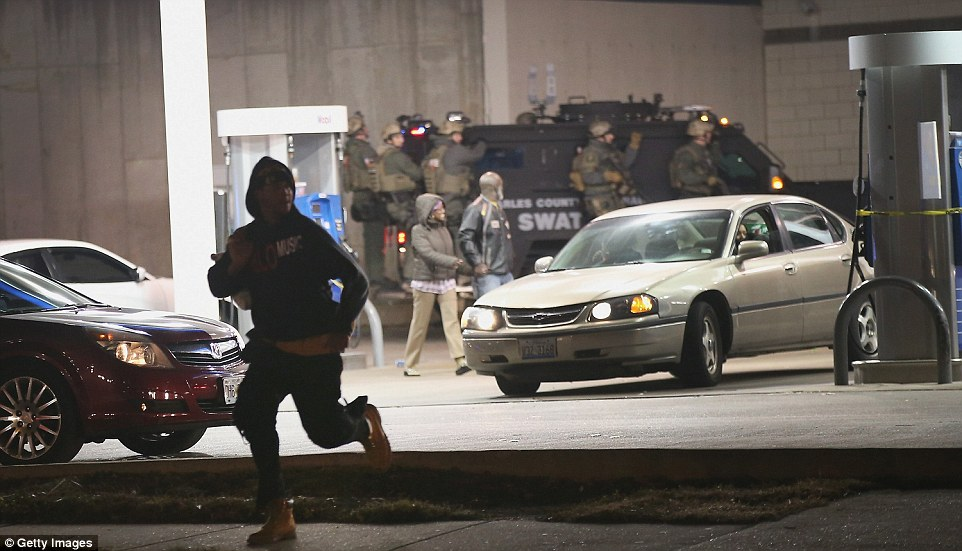Opportunist: Looters run from a gas station as police arrive during the rioting in a heavily armored SWAT vehicle