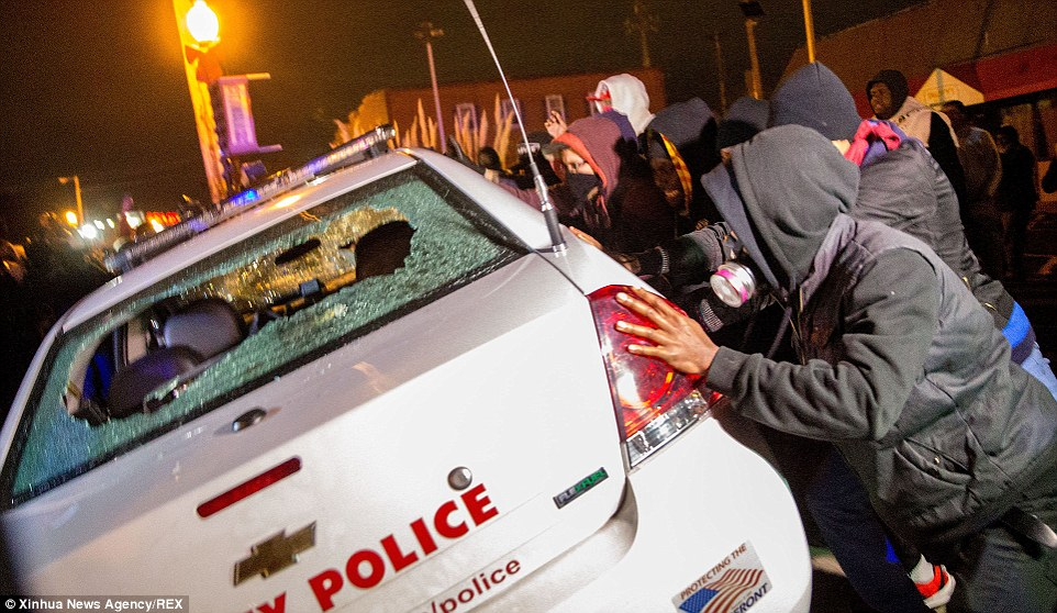 Anger: Demonstrators, many with their faces covered by scarves, try to push over a police car in Ferguson