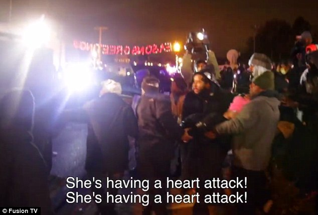 Concern: A group of protesters is seen carrying an apparently unconscious woman (pictured, in a pink hat) toward armored officers in the St Louis suburb of Ferguson, while screaming: 'She's having a heart attack'