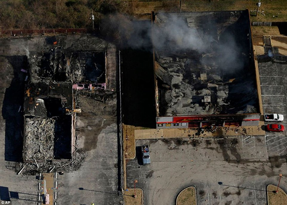Damage done: Two buildings still smoulder after the riots that ravaged Ferguson, Missouri overnight