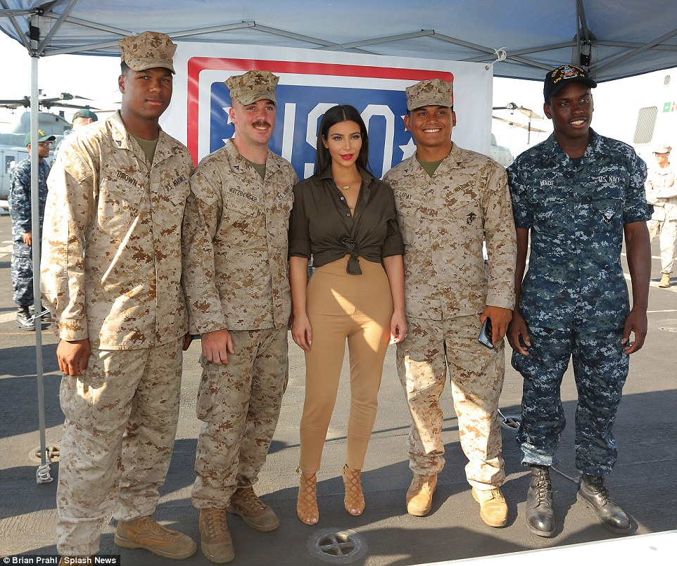 A man in uniform: Kim was happy to pose alongside several troops on the aircraft carrier which had just returned from South Africa