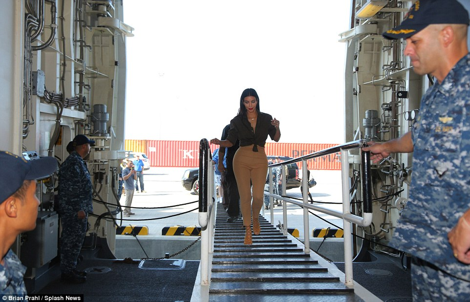 All aboard: The star tottered onto USS San Diego in a pair of towering strappy heels which matched her nude and olive green outfit