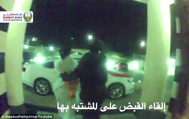 Dragged away: She is seen being led away in cuffs following the night-time raid on her home
