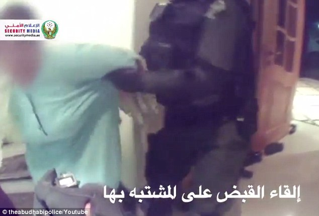 Caught: Footage released by the Abu Dhabi Police on Thursday shows them arresting a woman suspected on stabbing an American mother to death inside a mall restroom on Monday