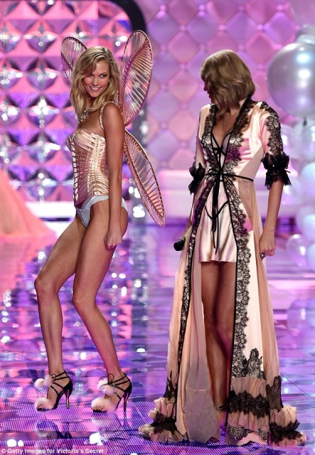 Cheeky: Karlie, 22, gave her pal a knowing glance as she took a turn on the catwalk at the Earl's Court Exhibition Centre in London