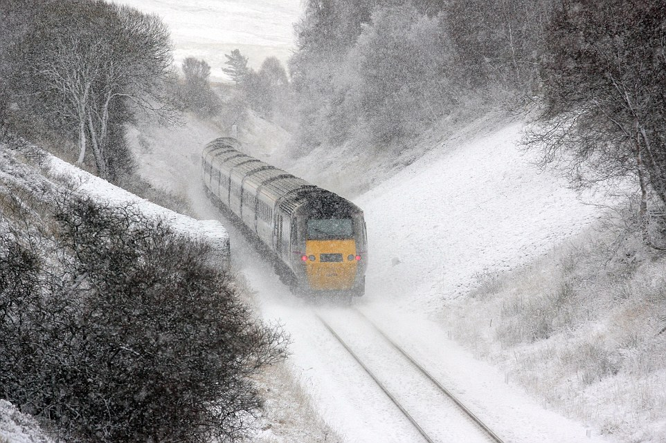 Cold snap: Temperatures dropped to almost -3C in parts of Britain last night, with forecasters warning the cold weather is set to continue this week, and bring with it more snow and gale-force winds. Pictured: A train battles through heavy snowfall in Inverness this morning