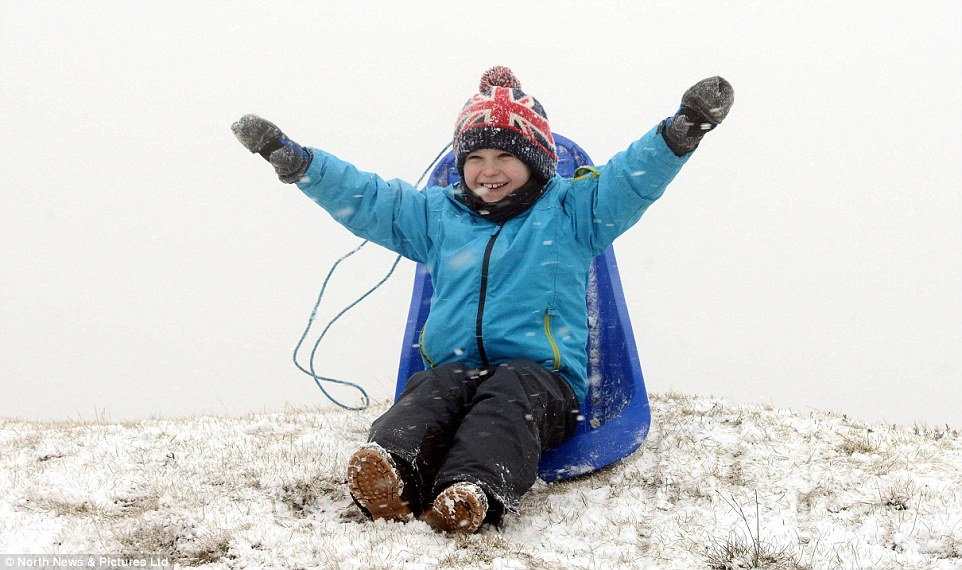 Fun in the snow! Eight-year-old Alex Kingston enjoys a sledge ride in  Northumberland today as heavy snowfall hit the north of the country