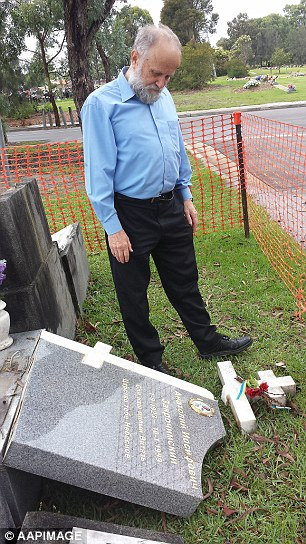 John Koudrin stands beside the grave of his former Russian language teacher Anatole Zakroczymski, which was destroyed
