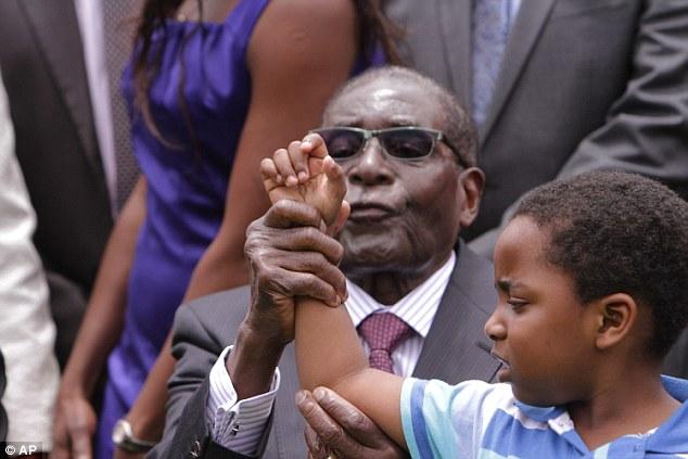 Zimbabwean President Robert Mugabe  attempts to make Dali Thando Phekezela Mphoko, the grandson of  his Deputy President, Phekezela Mphoko, chant the party's slogan in December last year