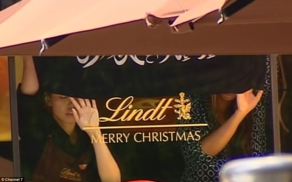 Dozens of people are being held hostage by a terrorist who stormed into a central Sydney cafe with a gun and forced crying women to hold a black Islamic flag up to the window