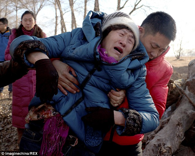 Shang Aiyun, the mother of Hugjiltu, is dragged away from his tomb amid howls of anguish from the family