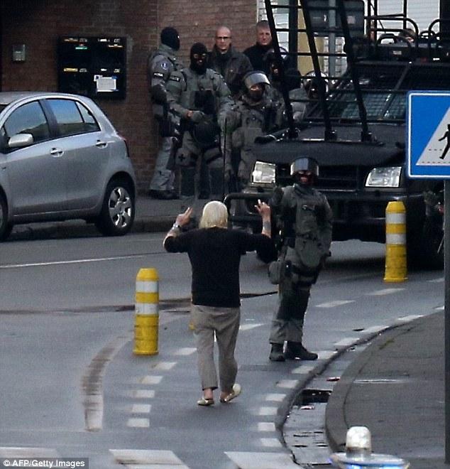 Un secuestrador sospechoso, a la izquierda, se entrega a la policía después de que cuatro hombres armados invadieron un apartamento en la ciudad belga de Gante hoy