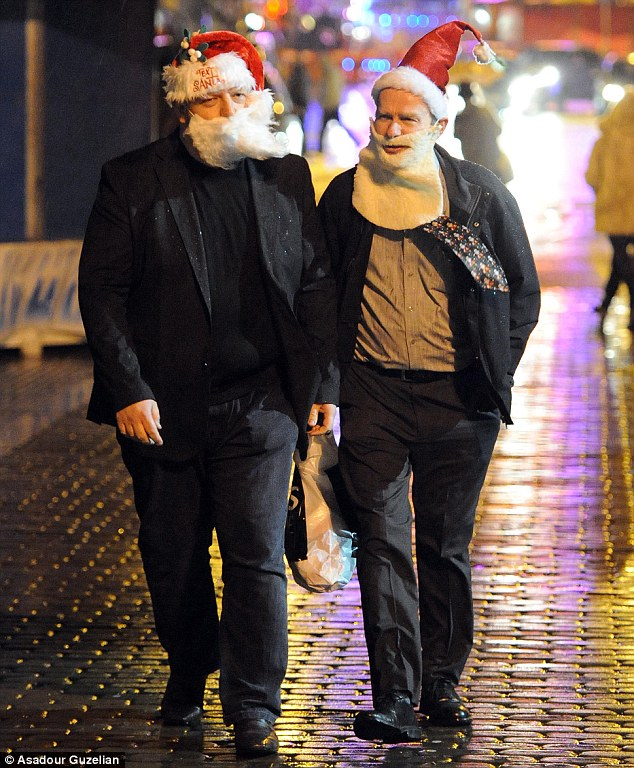 Two men get in the festive spirit as they march through the Leeds city centre in Santa hats and beards