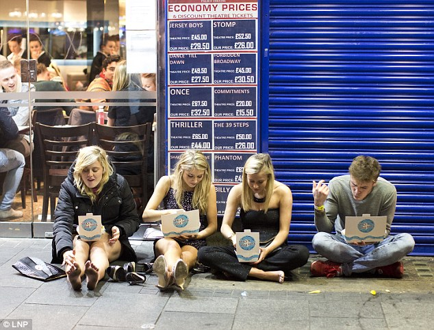 A group of friend eat fast food on the street after celebrating the start of the Christmas holidays