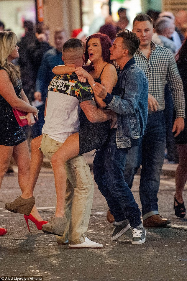 A woman is lifted up by two men while out celebrating in Swanseaas many offices closed for the festive period