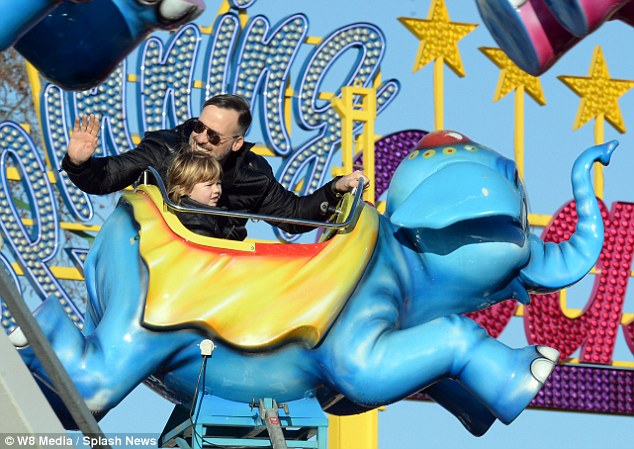 All smiles: David gave a wave as he took his eldest son around on the Dumbo ride in Hyde Park