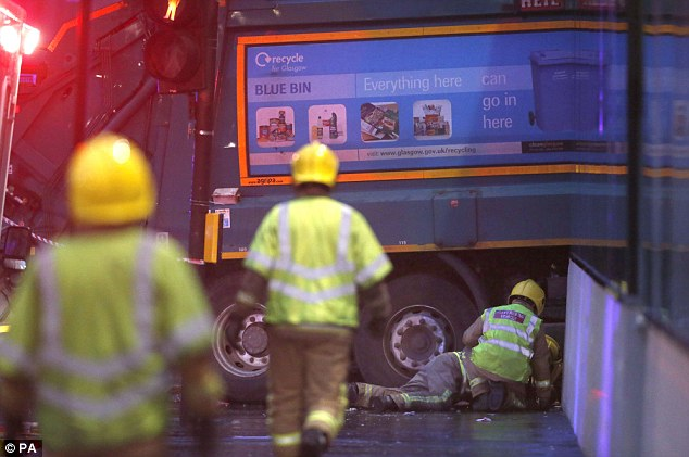 A firefighter reaches under the council bin lorry whose driver reportedly suffered a seizure or heart attack