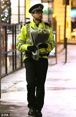 A police officer takes a bunch of flowers to lay at the crash site