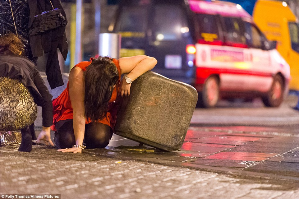 All too much: A girl kneels on the ground, propped against a bollard, after a night of partying