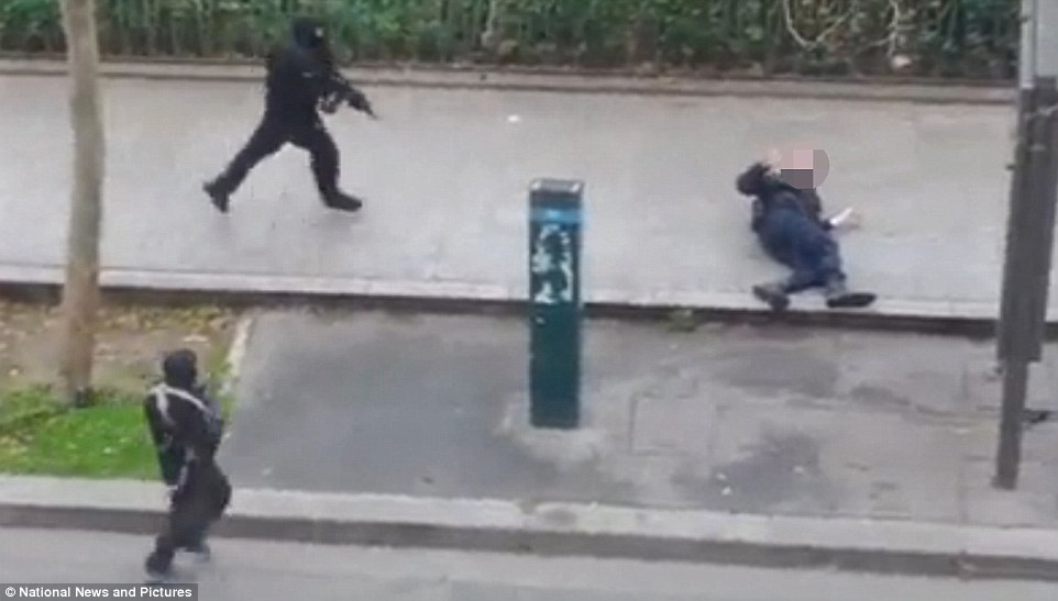 Gunned down in cold blood: Horrific footage shows the injured police officer slumped on the pavement as two of the gunmen approach. In a desperate plea for his life, the officer slowly raises his hand towards one of the attackers, who callously shoots him at point-blank range